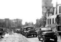 A convoy of U. S. equipment and men moving through a liberated town after being cleared by engineers