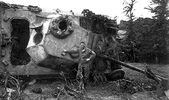 Engineer posing with a destroyed German tank