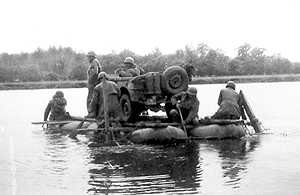 Ferry with jeep crossing a river by engineer power